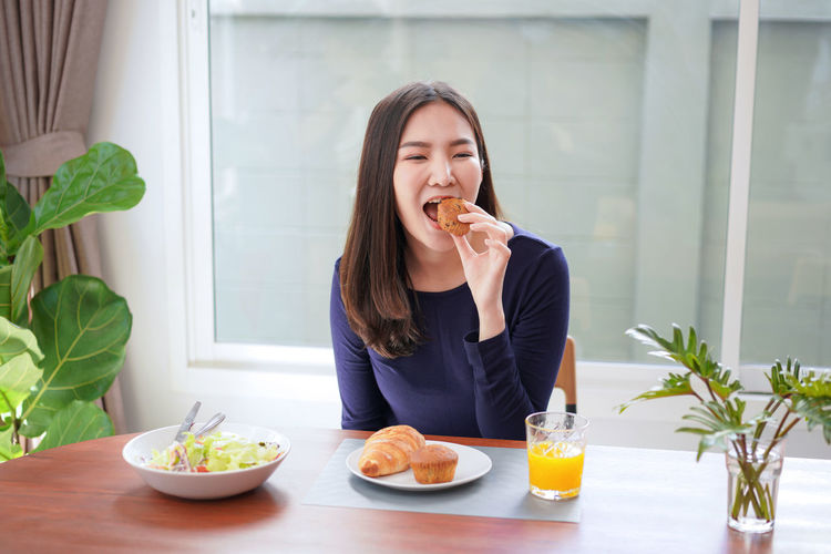 Young woman eating food at home