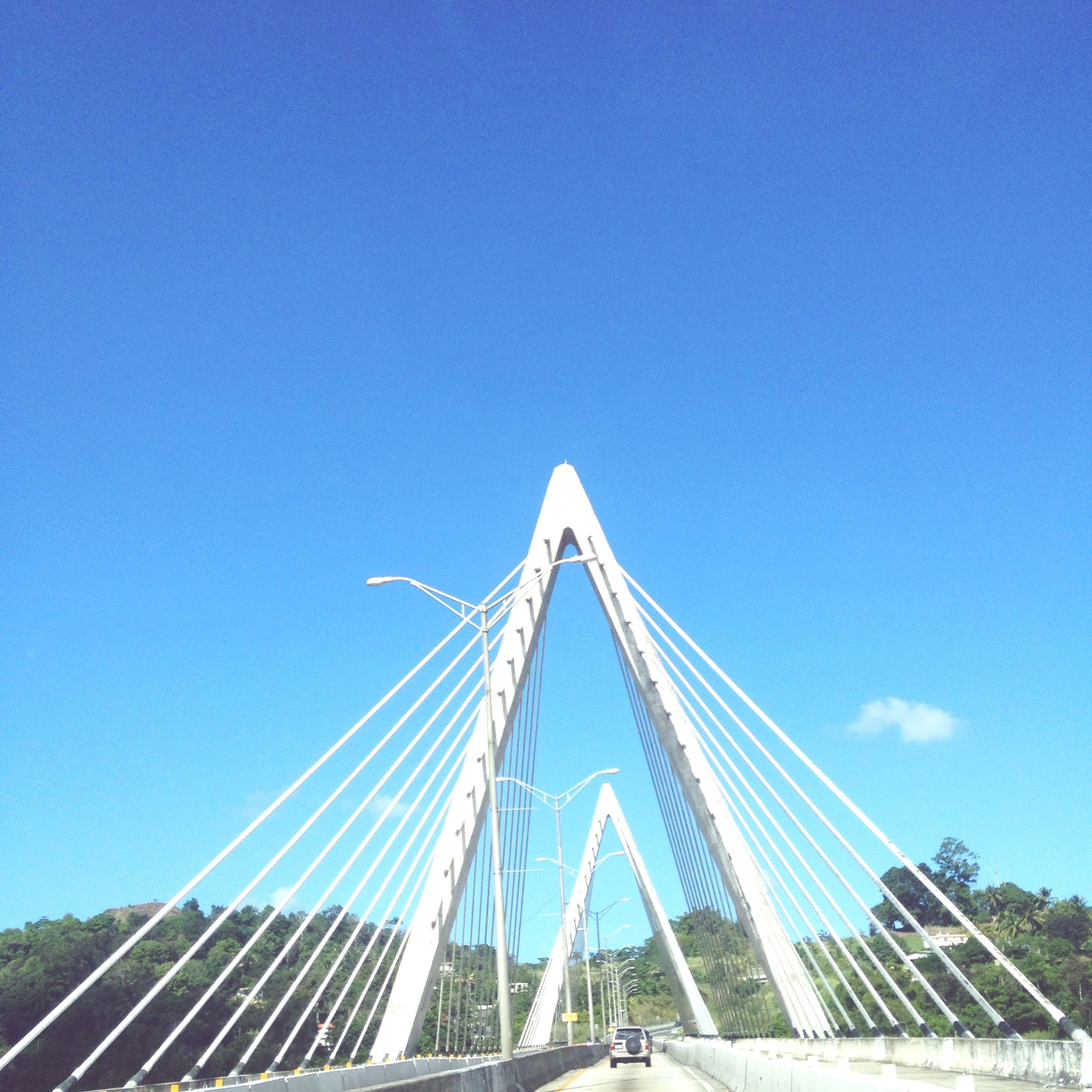 blue, clear sky, low angle view, transportation, copy space, built structure, nautical vessel, connection, day, mode of transport, outdoors, architecture, sky, engineering, suspension bridge, sunlight, part of, no people, travel, rope