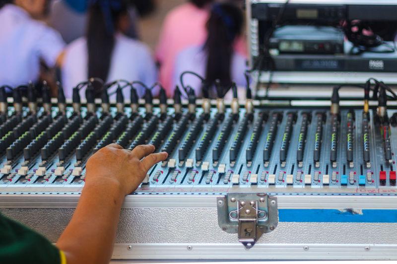 Close-up of musician hand adjusting audio equipment