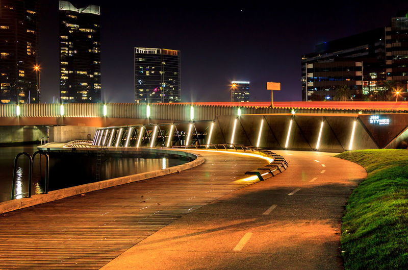 Illuminated bridge by buildings in city at night