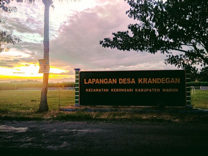 Information sign on field against sky during sunset
