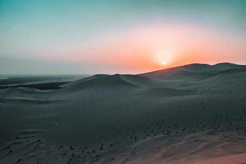 Scenic view of desert against sky during sunset