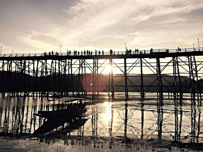 Silhouette bridge over pier against sky during sunset