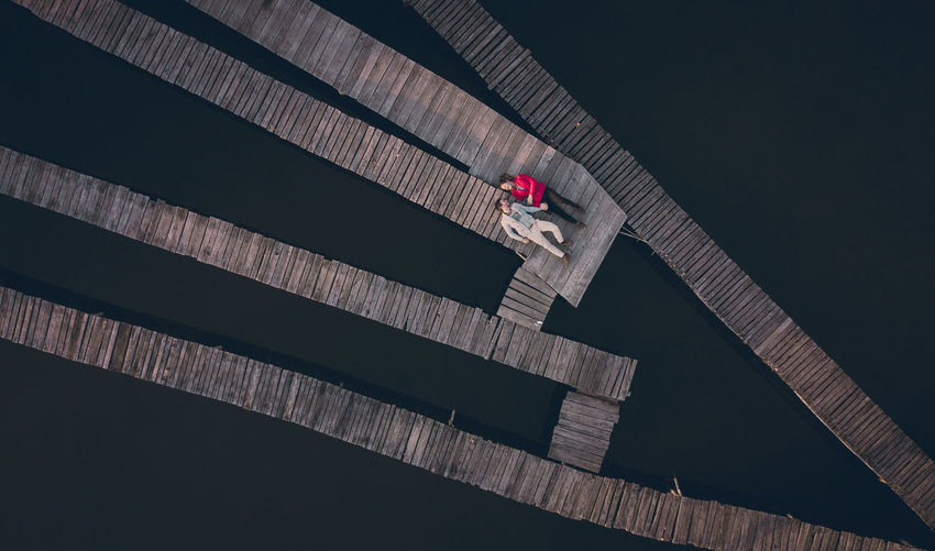 High Angle View Of Couple Lying On Pier Over Lake