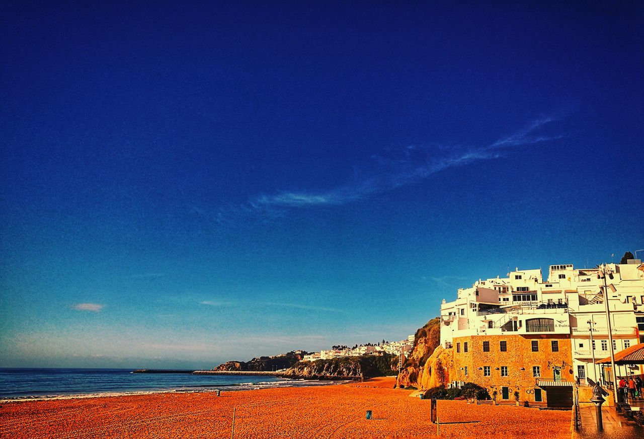 sea, blue, architecture, building exterior, nature, built structure, beach, outdoors, day, sky, beauty in nature, scenics, tranquility, travel destinations, vacations, sand, no people, horizon over water, water