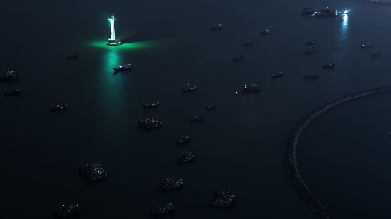 High angle view of boats sailing on sea at night