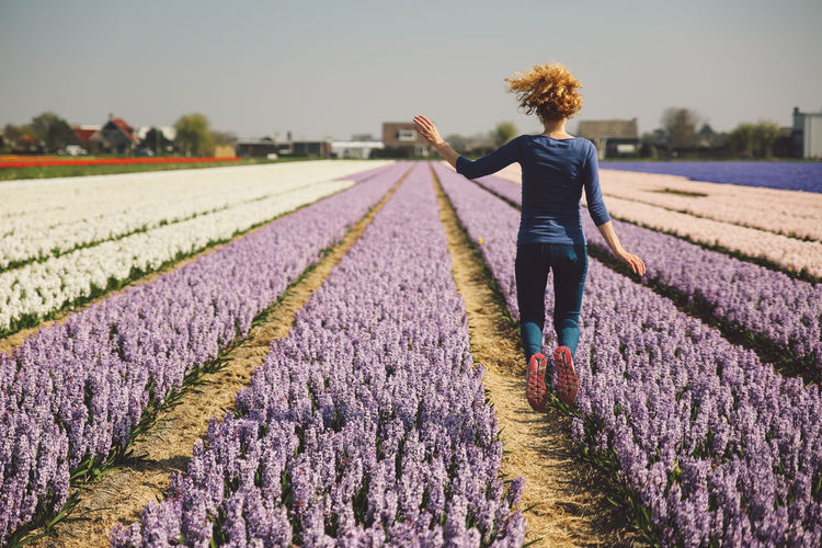 Rear view of woman jumping in flower field