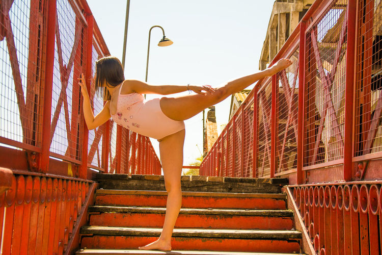 Woman wearing leotard dancing on staircase against clear sky
