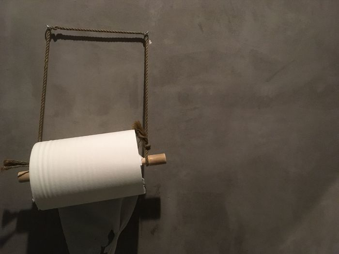 Close-up of toilet paper hanging against wall