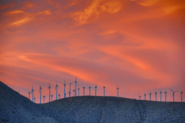 Low angle view of windmills of mountain peak during sunset