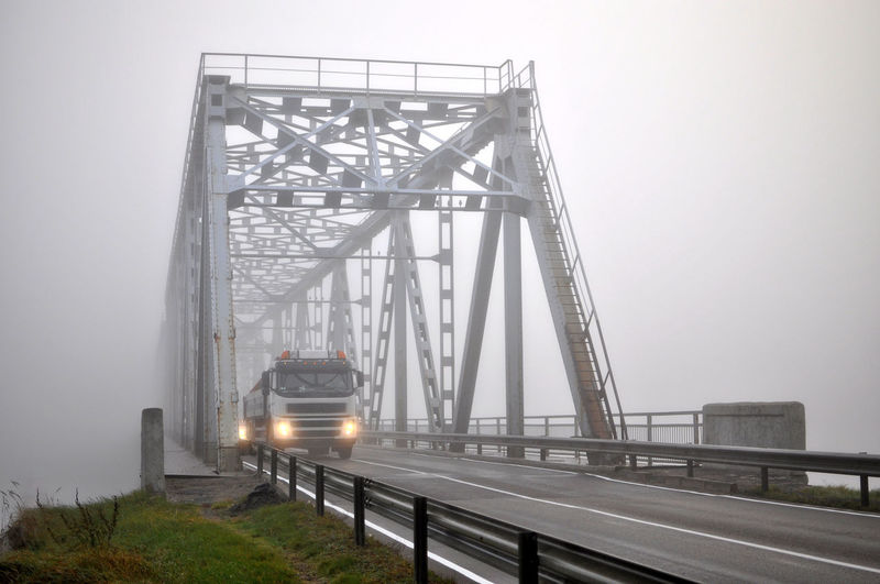 Truck Moving On Foggy Bridge Against Sky