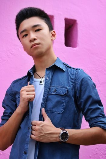 Portrait Of Young Man Standing Against Pink Wall