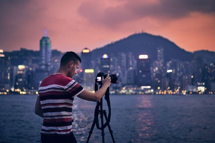 Man photographing river in city at dusk