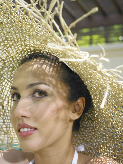 Close-up of young woman in sun hat