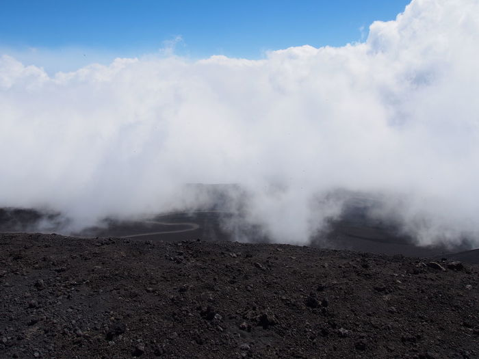 Scenic View Of Steam Emitting From Volcanic Landscape Against Cloudy Sky