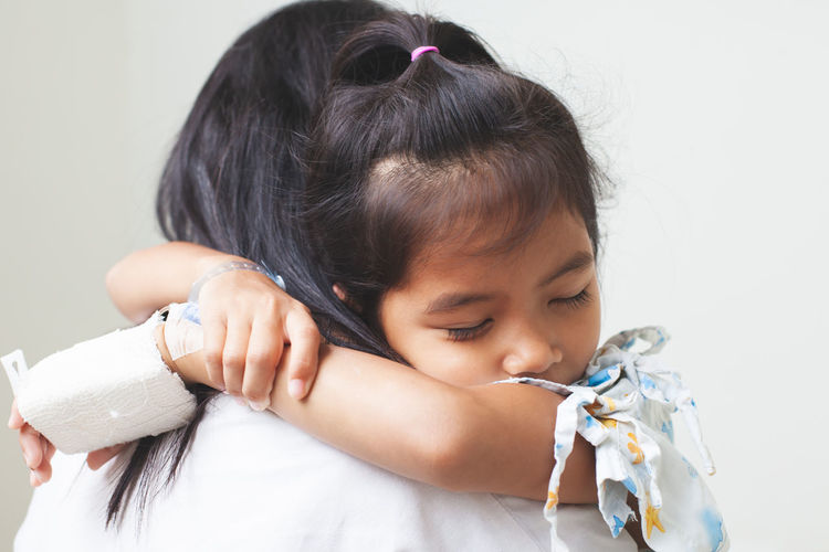 Mother carrying sick daughter against wall in hospital