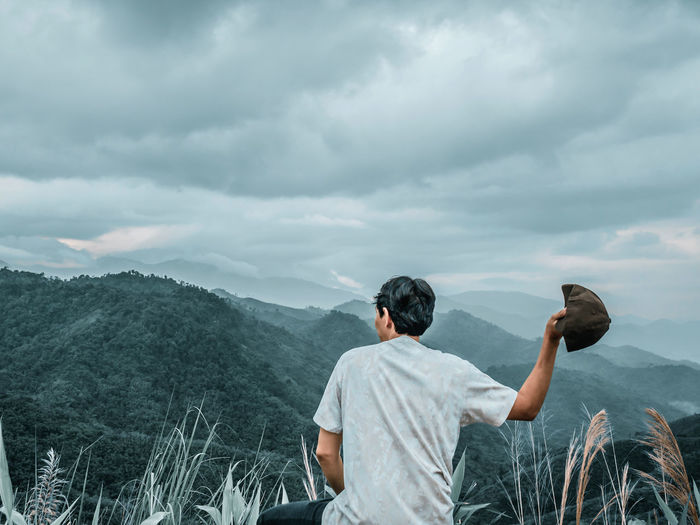 Rear view of man throwing cap against mountain and cloudy sky
