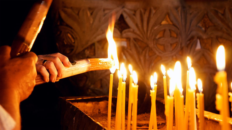 Cropped hands holding illuminated candles at church