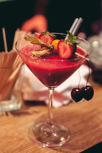 Close-up of fruit drink in martini glass on table