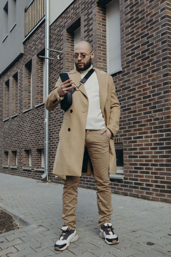 Full length of young man using mobile phone against brick wall
