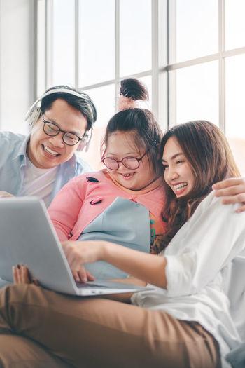 Cheerful family looking at digital tablet at home