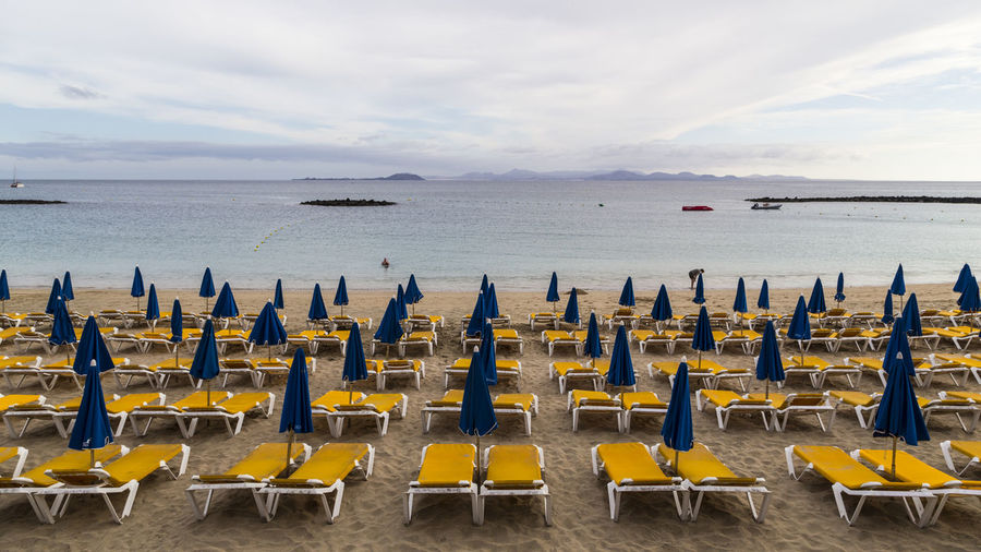 In Playa Blanca, Lanzarote Beach Life Lanzarote Playa Blanca Absence Beach Beauty In Nature Chair Cloud - Sky Empty Horizon Horizon Over Water In A Row Lounge Chair Nature No People Order Outdoors Scenics - Nature Sea Seat Side By Side Sky Tranquil Scene Tranquility Water