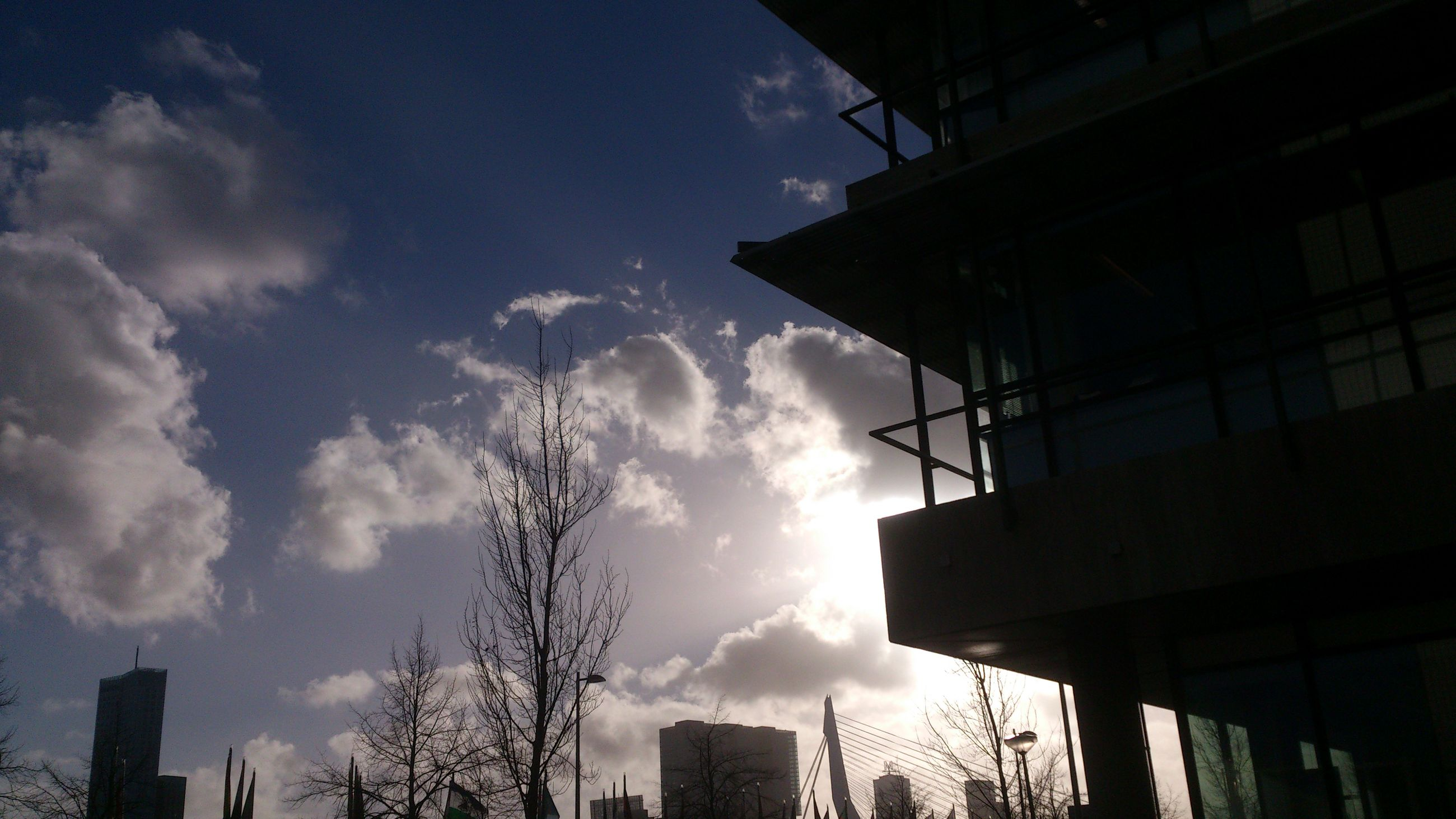 building exterior, architecture, built structure, low angle view, sky, cloud - sky, building, city, silhouette, cloud, residential building, residential structure, sunlight, window, house, cloudy, outdoors, sunbeam, no people, day