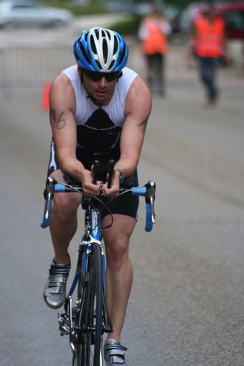 Sports Photography Cycling TRIATHLON Athlete On The Road Competition Going The Distance Race Front View Expression Capture The Moment Outdoor Photography Celebrate Your Ride Start Number Sport In The City Sport Way Of Life Challenge