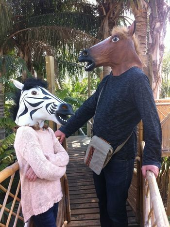 Animal Head  Animal Themes Casual Clothing Child Day Family Front View Full Length Fun Times Having Fun Horses Leisure Activity Lifestyles Mask Outdoors Person Railing Rear View Sitting Standing Three Quarter Length Tree Wood - Material Young Adult Young Women