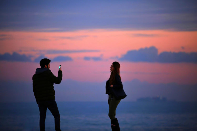 shooting by phone Sky Sunset Standing Cloud - Sky Silhouette Two People Adult Men Three Quarter Length People Beauty In Nature Nature Togetherness Women Scenics - Nature Technology Orange Color Land Leisure Activity Young Adult Couple - Relationship International Women's Day 2019