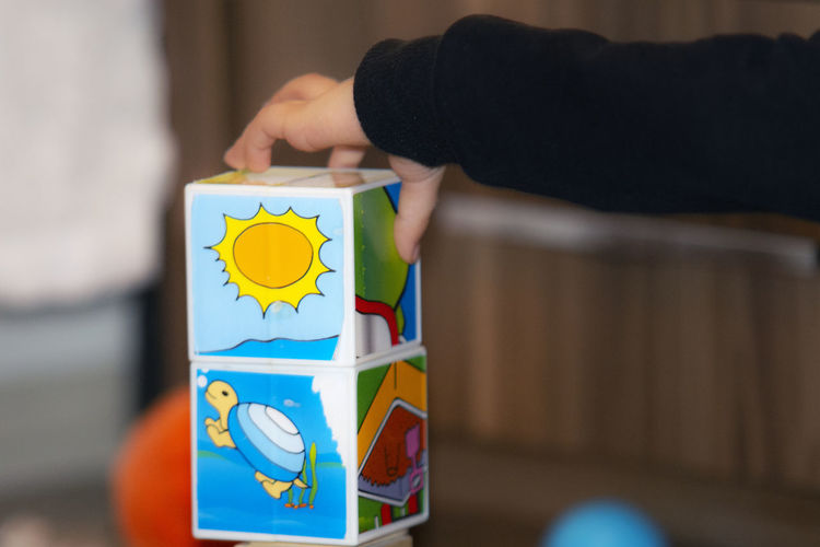 Human Hand One Person Human Body Part Hand Childhood Child Offspring Holding Toy Block Indoors  Lifestyles Multi Colored Selective Focus Midsection Leisure Activity Real People Close-up Men Body Part Human Limb