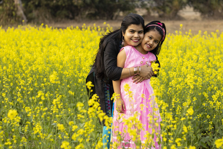 A pretty indian mother hugging her daughter and standing in yellow mustard flower field
