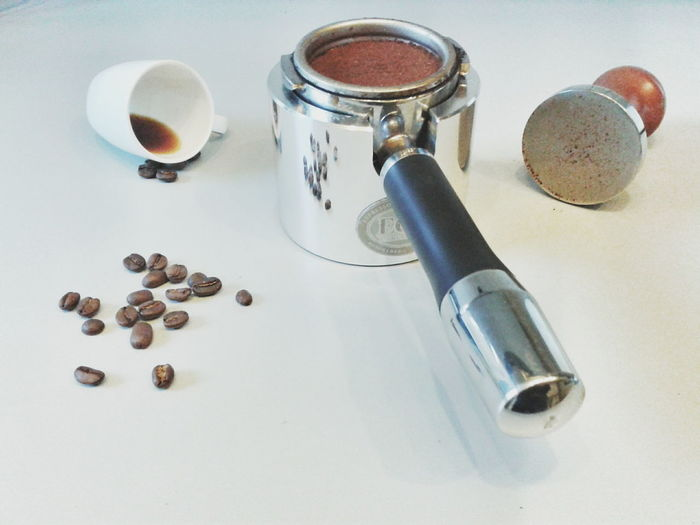 Portafilter With Coffee Beans And Metal Tamper On Table