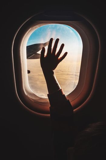Cropped Hand Touching Window While Traveling In Airplane
