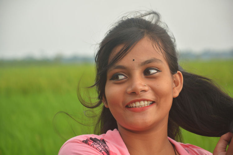 Portrait of smiling young woman on field