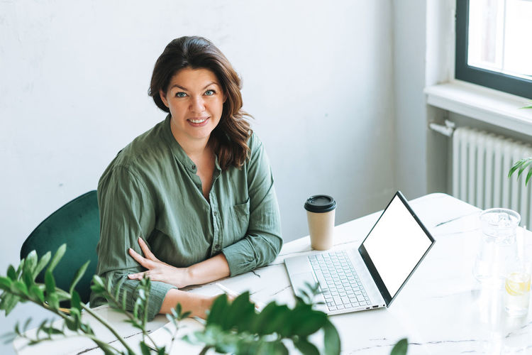 Portrait of smiling young woman using laptop on table
