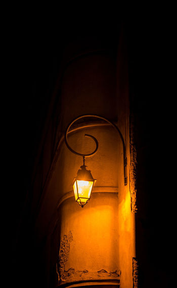 Low angle view of illuminated lamp hanging on wall in building