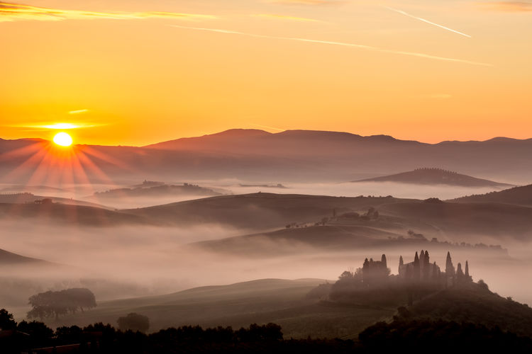 Scenery sunrise in Tuscany, Italy. Misty morning with light fog shapes magically the hills and valleys of this beautiful picturesque travel location of San Quirico d'Orcia region Tuscany Tuscany Countryside Architecture Beauty In Nature Cloud - Sky Environment Fog Idyllic Landscape Mountain Mountain Peak Mountain Range Nature No People Non-urban Scene Orange Color Outdoors Scenics - Nature Sky Sun Sunlight Sunrise Sunset Tranquil Scene Tranquility Tuscany Italy The Traveler - 2018 EyeEm Awards