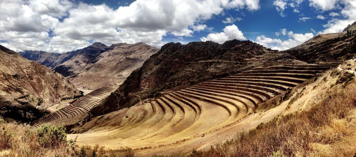 Inca ruins by mountains against sky