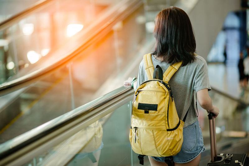 Rear view of woman with luggage standing on moving walkway