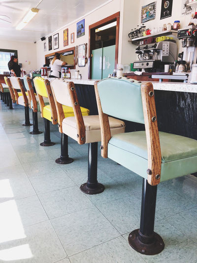 Empty chairs and tables on tiled floor