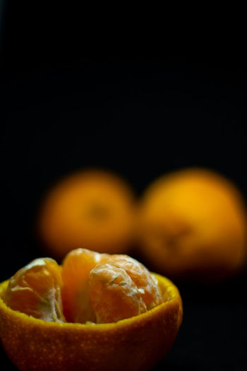 Close-up of oranges on table against black background