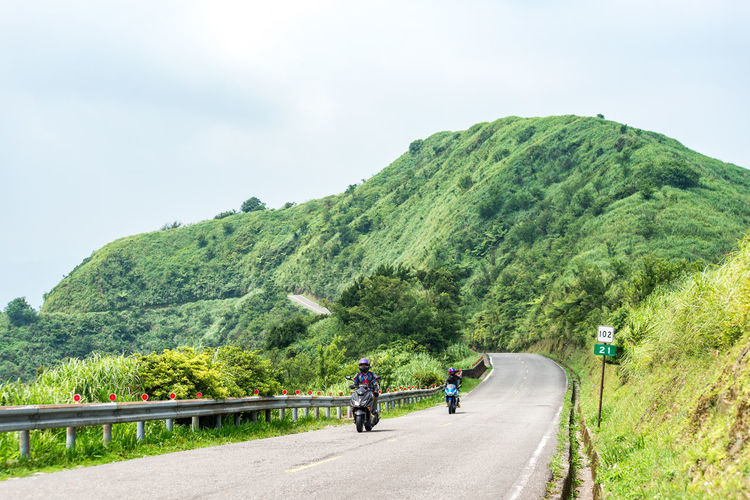 Transportation Plant Road Tree Mountain Nature Real People Sky Beauty In Nature Day The Way Forward Direction Green Color Group Of People Mode Of Transportation Scenics - Nature Mountain Range Growth Non-urban Scene Lifestyles Outdoors Riding Mountain Road