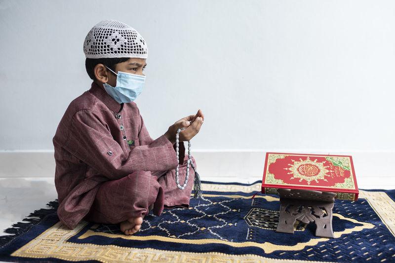 Full length of boy wearing mask praying at home