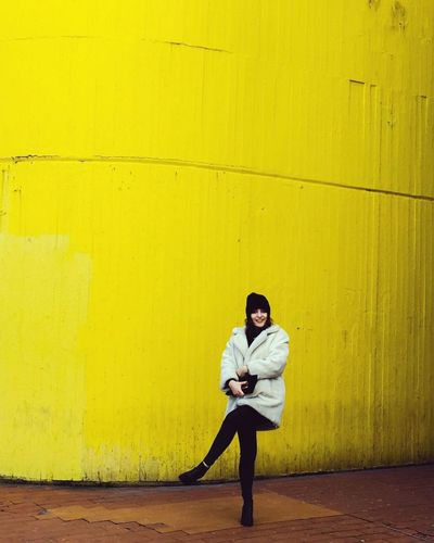 Full length of woman against yellow wall