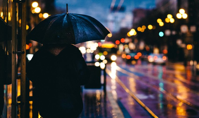 Rear view of man with umbrella standing on street at night during rainy season