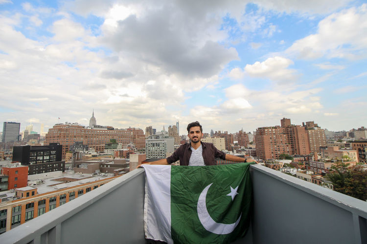 Portrait of man standing holding pakistani flag