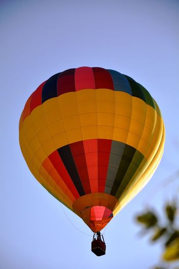 Low angle view of hot air balloon flying in clear blue sky