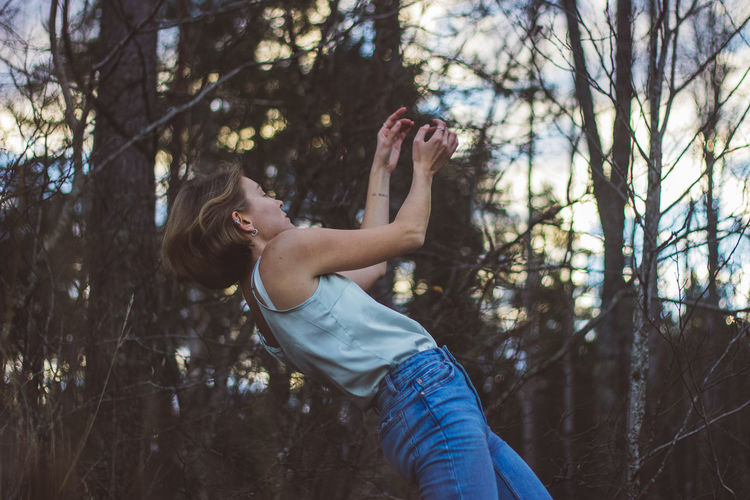 Side view of young woman dancing against trees in forest