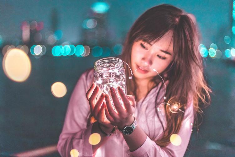 Portrait of young woman holding illuminated mask